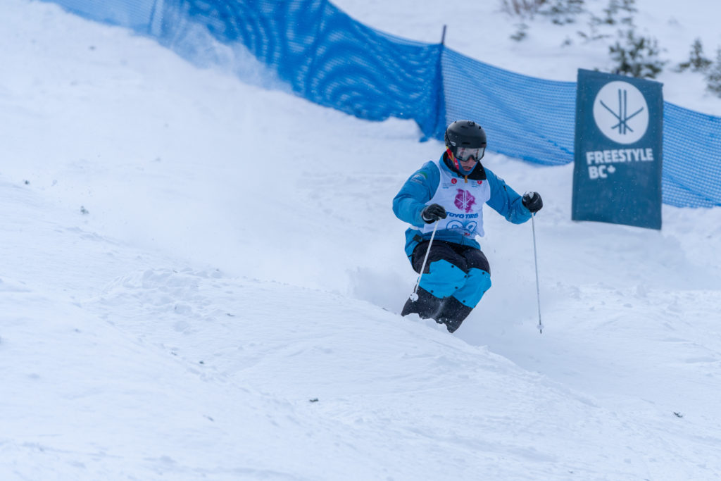 A person riding a snowboard down a snow covered slope  Description automatically generated