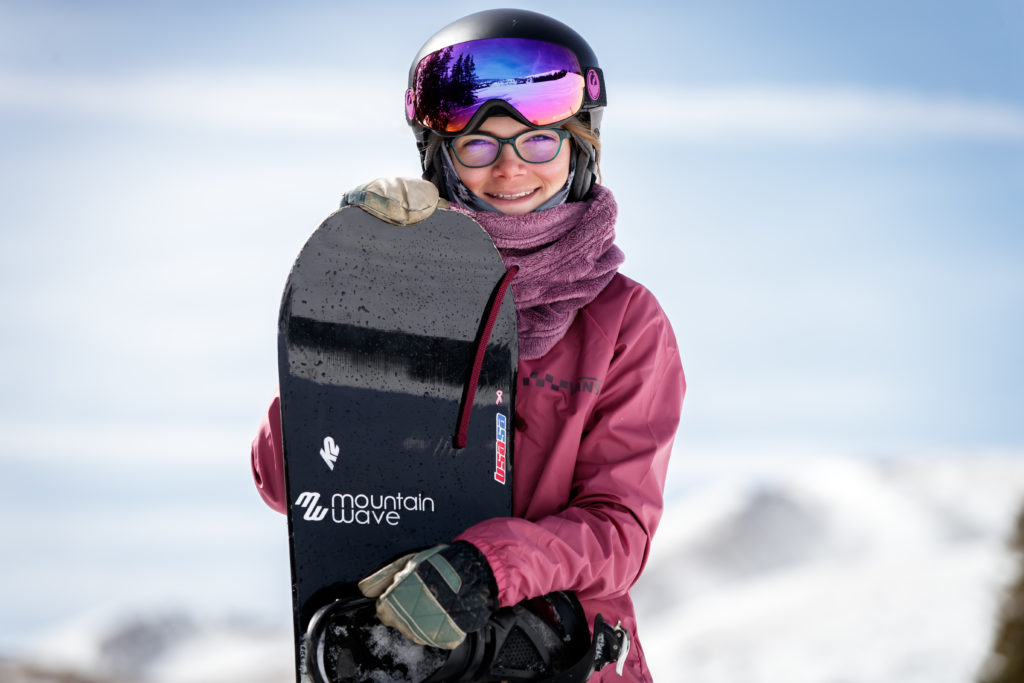 A person wearing a helmet posing on a snow covered slope  Description automatically generated